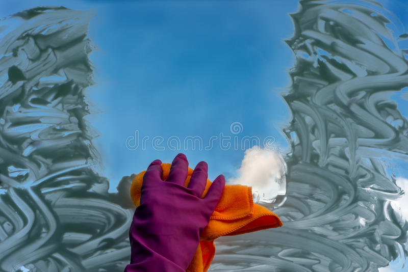 A hand in a glove washes the window royalty free stock images