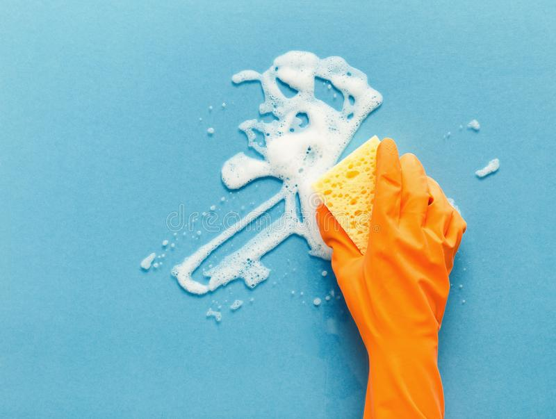 Hand in glove washing glass surface with sponge and cleaning foam royalty free stock photos