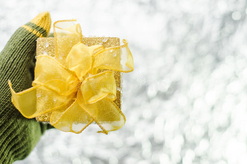 Download Hand In Gloves Holding Gold Christmas Gift Box Stock Photo - Image: 83701799