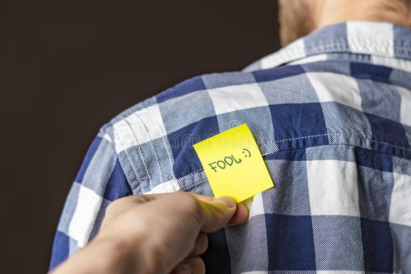 Hand glue yellow kick me sticker on persons back at aprill fool day b royalty free stock images