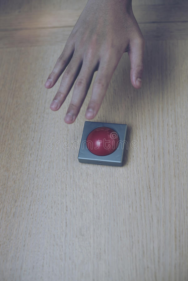 Free Hand Grab For The Red Button On Wood Table. Royalty Free Stock Photography - 79610227