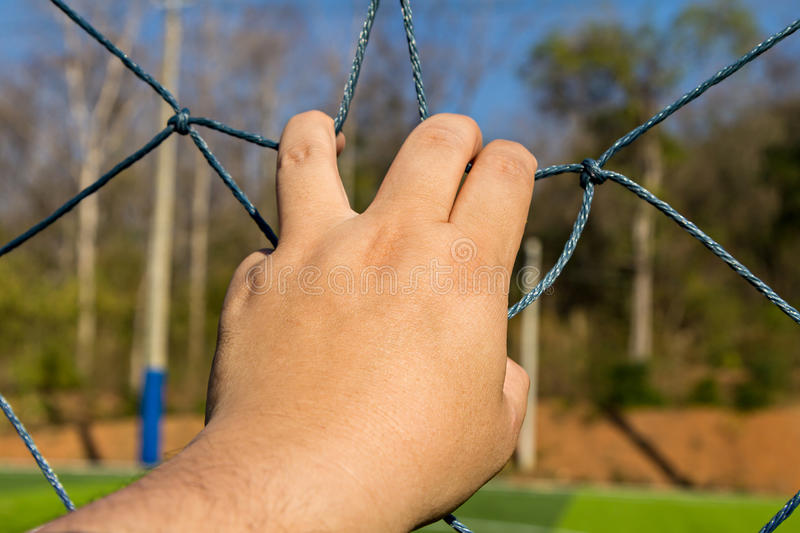 Hand grab the rope mesh. Fence royalty free stock image