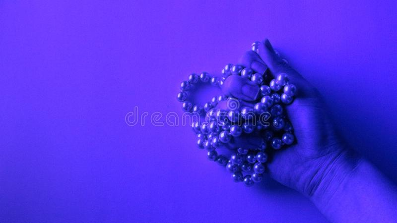 Hand grabbing pearl necklace below neon light. With copy space to insert text. Wide screen, flat lay view stock photo