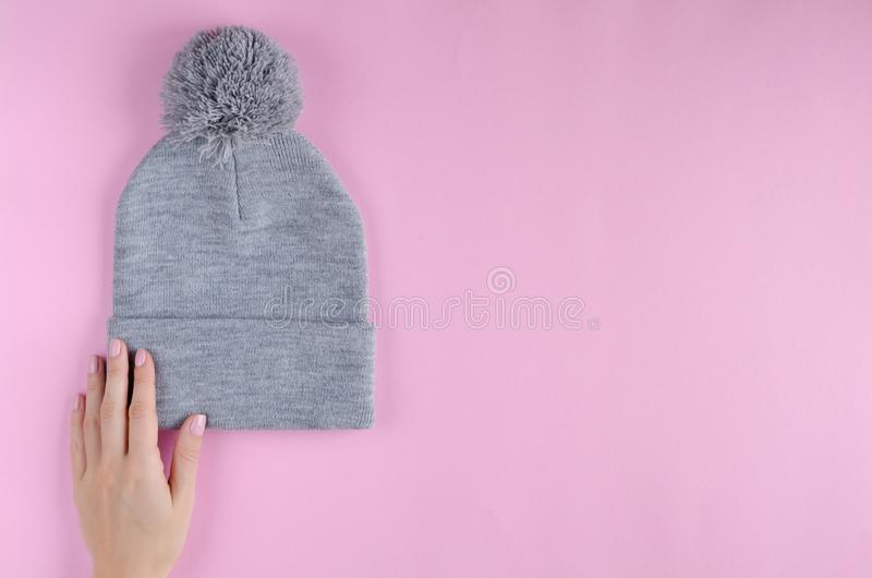 Hand with gray cotton hat composition on pink background. Flat lay, layout and tabletop mockup with copy space, above, flatlay, view, desk, frame, overhead stock photo