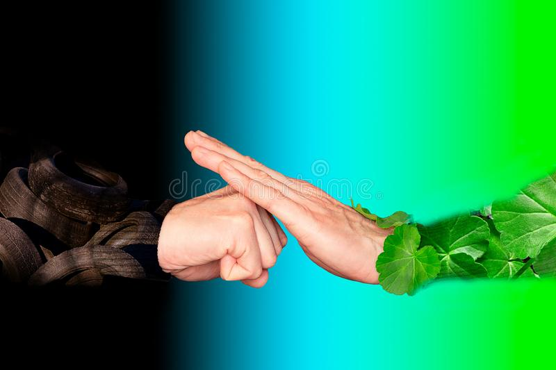 Hand in green foliage symbolizing nature is opposed to compressed in a fist and the striking hand with the clothes of automobile stock photography