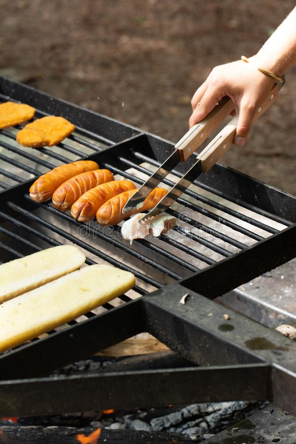 Barbecue over a fire. A hand with a grill tongs turns meat on the grill royalty free stock photos