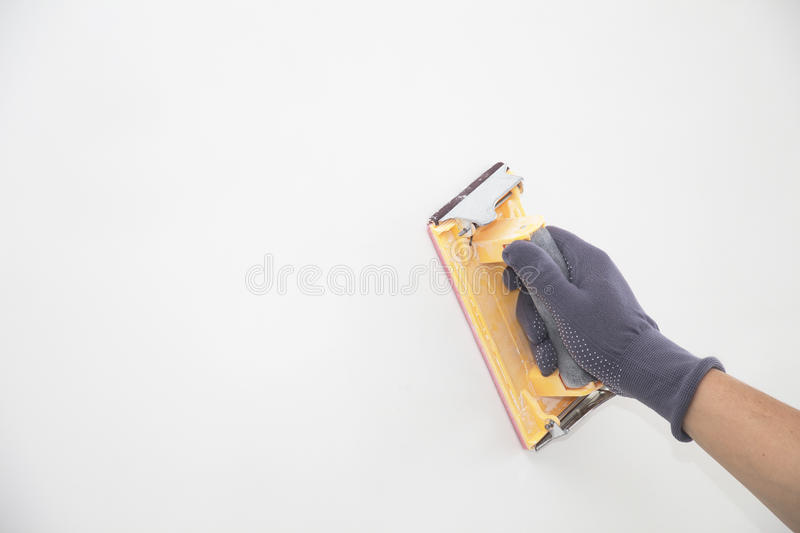 Hand grinding wall with sandpaper stock photography