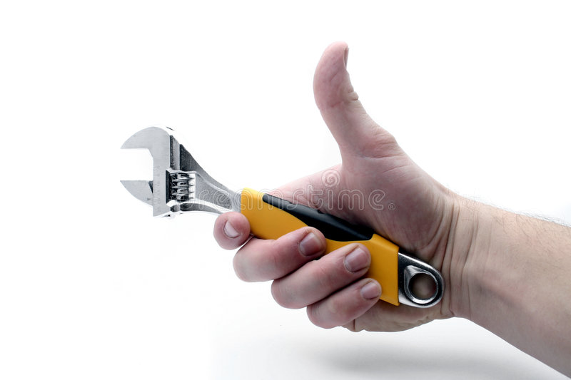 Hand grips adjustable wrench. A studio view of a hand holding a medium size adjustable wrench with a yellow handle. Isolated on a white background royalty free stock images