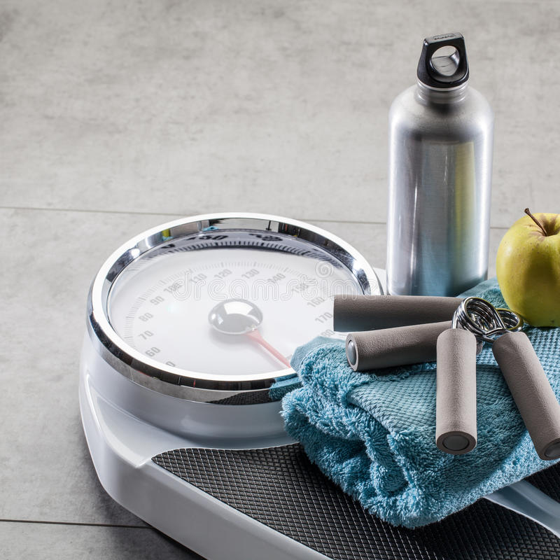 Hand grips, aluminium flask and apple on gym floor, copyspace. Scales after training, workout and healthcare control with hand grips, aluminum flask and apple stock image