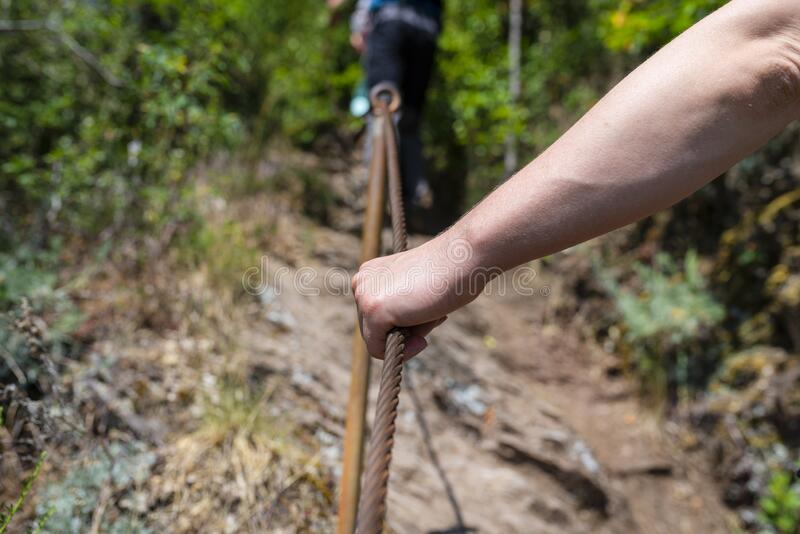 A hand grips the metal line firmly in the vineyards on a steep slate trail. A hand grips the metal line firmly in the vineyards on a steep slate trail stock images