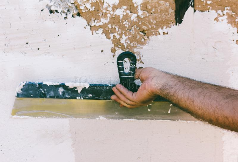 Hand guest worker with a steel spatula plastering the wall royalty free stock photography