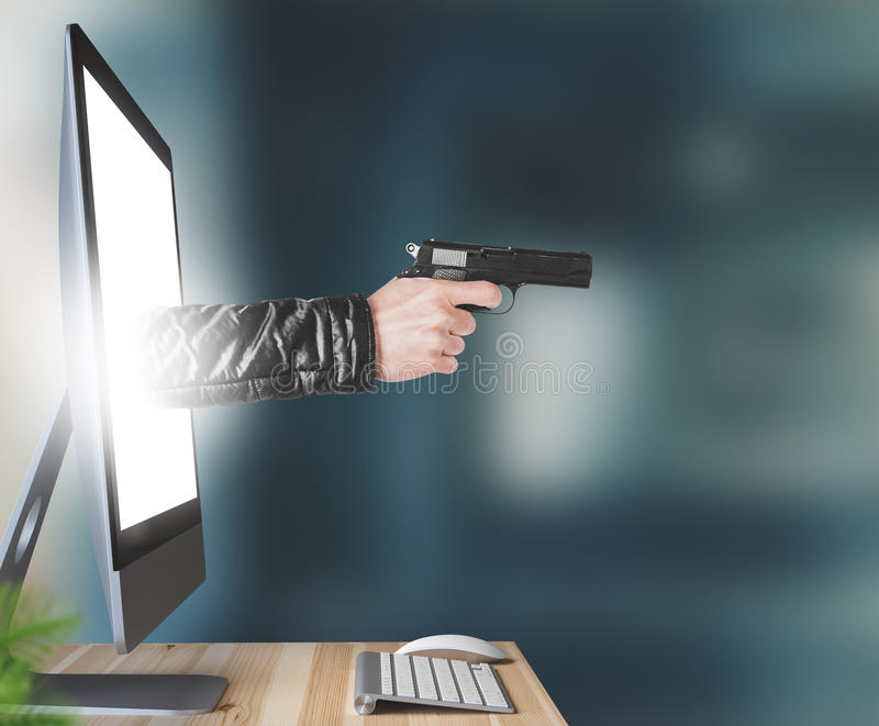 Hand with gun comes out of computer royalty free stock image