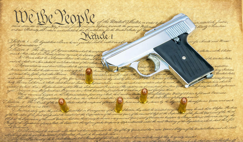 Hand gun on Constitution. Pistol and Bullets and the constitution stock image