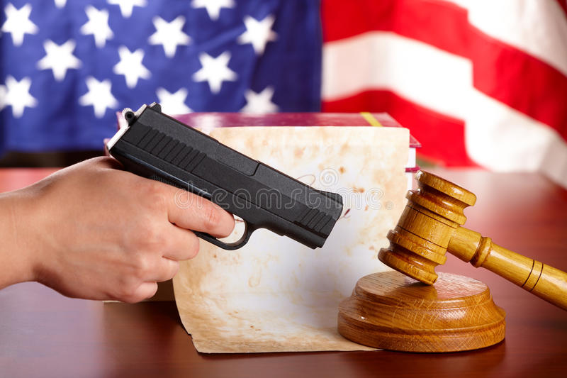 Hand with gun and judges gavel royalty free stock photography