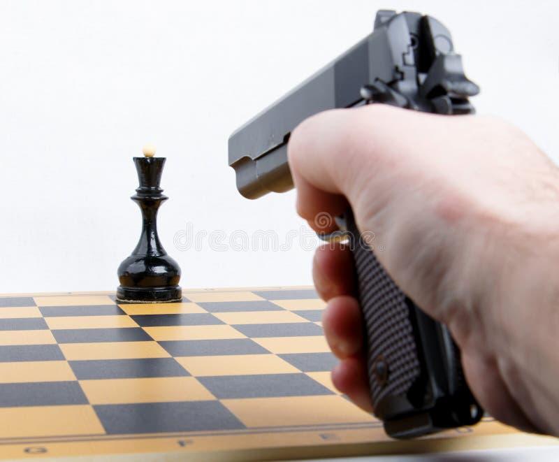 Hand with gun took aim at chess piece stock photos