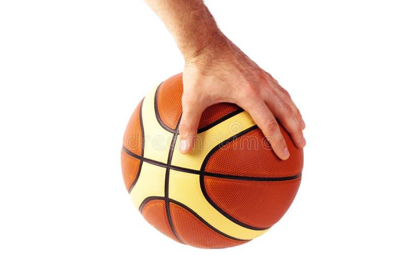 Hand hält Basketballball lokalisiert auf weißem Hintergrund stockfotografie