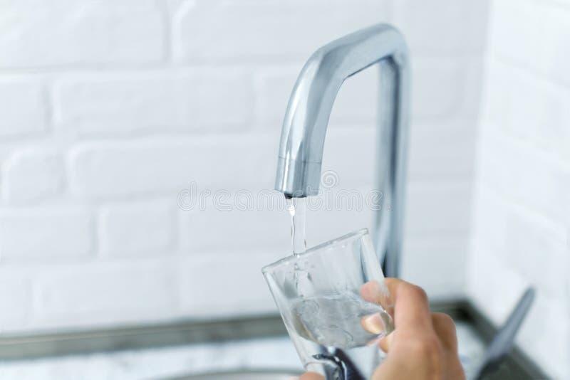 Hand hält das Glas und füllt es mit Wasser vom Hahn stockbild