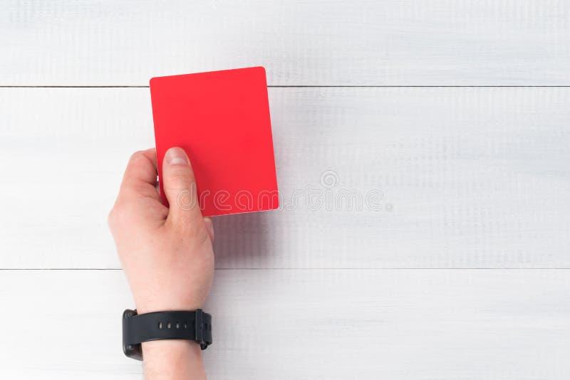 Hand hält eine rote Karte für Verletzung auf einem Fußballspiel, Nahaufnahme lizenzfreies stockbild