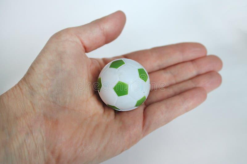 Hand hält einen kleinen Fußball stockbilder