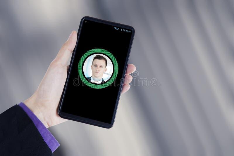 Hand hält einen Smartphone mit Gesichtsidentifizierung stockfotografie