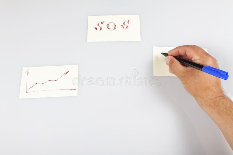 Hand hält einen Stift und schreibt auf einen Aufklecker stockbild