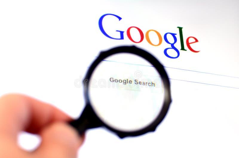 Hand hält Lupe gegen Google-homepage stockfoto