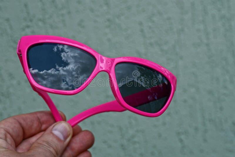 Hand hält rote Plastiksonnenbrille stockfotos