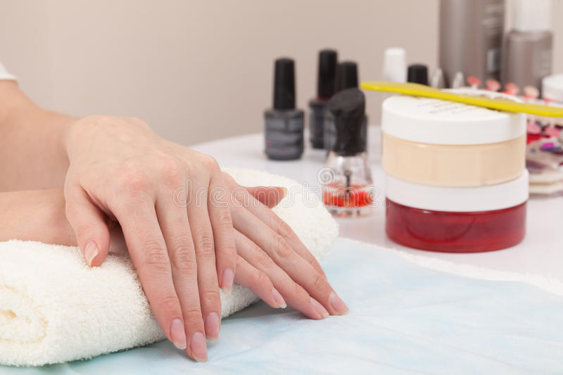 Hand on hand in nail salon stock images