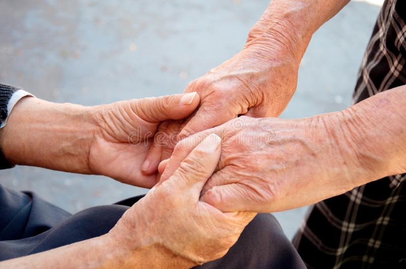 Hand in hand. Older people hold each other`s hands. stock photos
