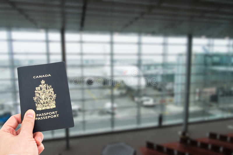 Hand handing Canadian passport. With airplane in background, boarding concept royalty free stock photography