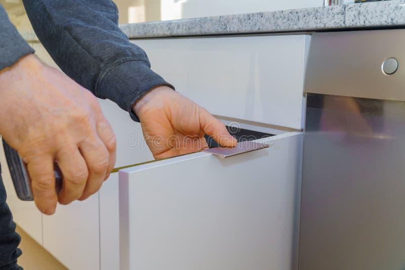Hand on handle installation door in kitchen cabinet. Hand on handle installation of door handles on opening cabinet door in kitchen stock images
