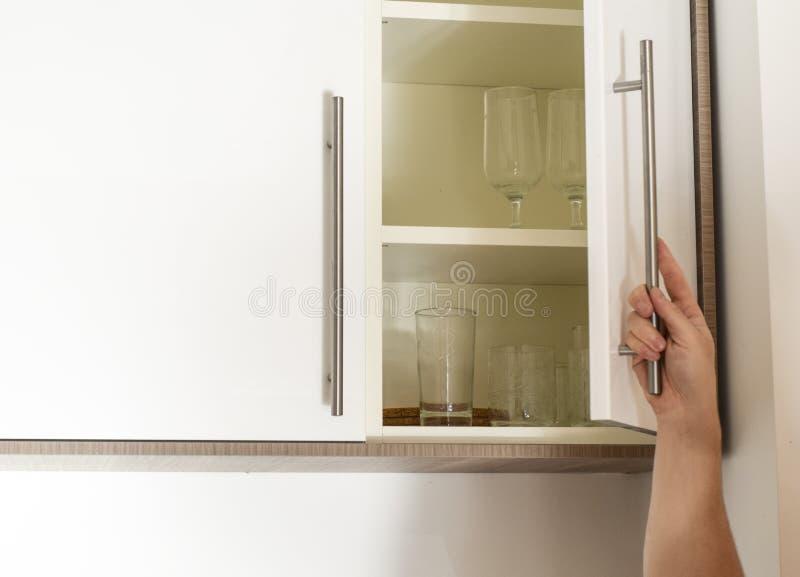 Hand on handle opening cabinet. Door in kitchen stock photo