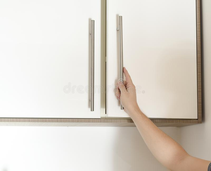 Hand on handle opening cabinet. Door in kitchen royalty free stock photo