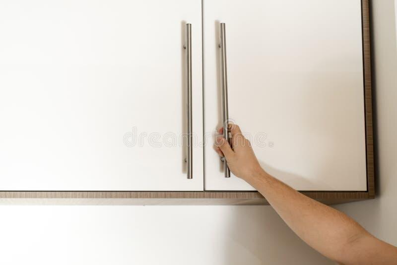Hand on handle opening cabinet. Door in kitchen stock photography