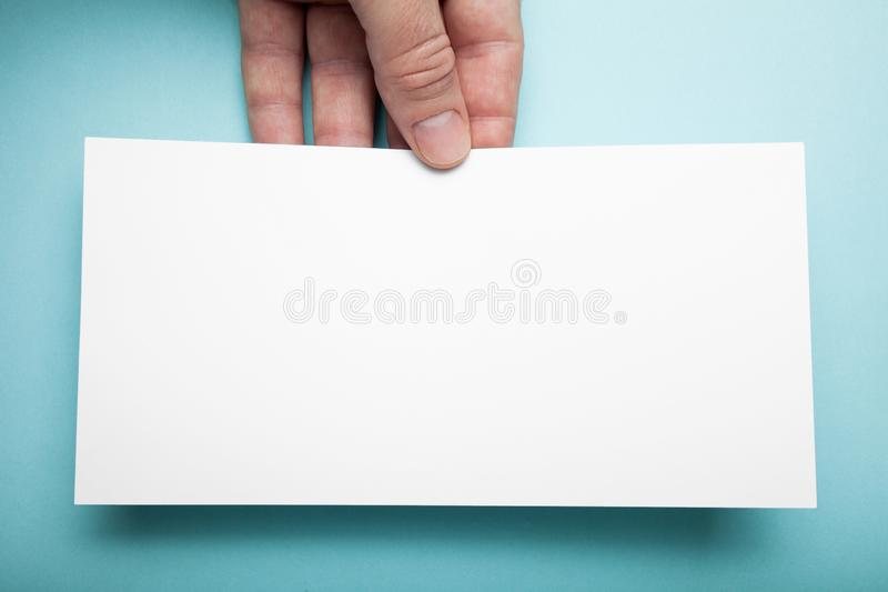 Hand hands holding a blank DL flyer on a blue background.  royalty free stock photography