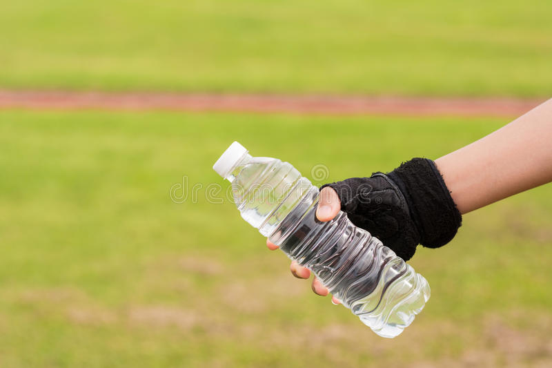Hand of healthy woman with gloves Holding fresh water bottle royalty free stock photos
