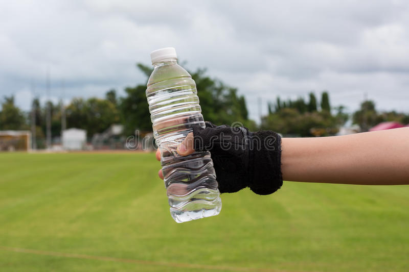 Hand of healthy woman with gloves Holding fresh water bottle stock photo