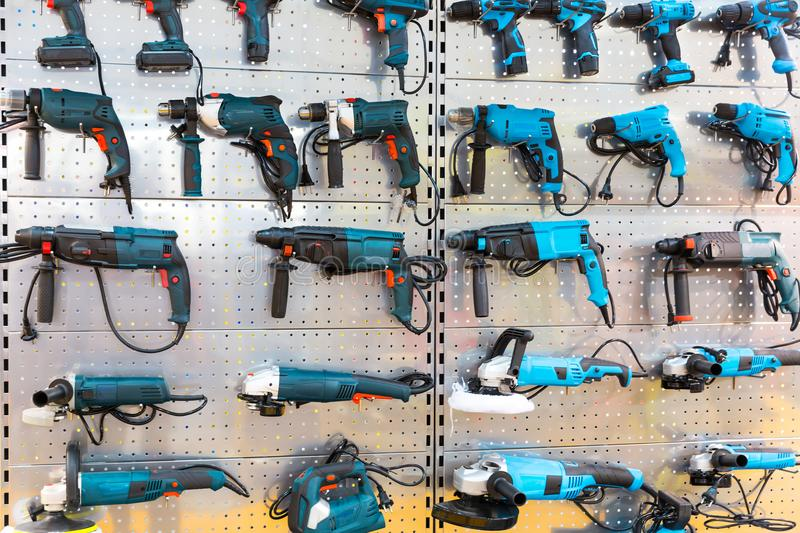 Hand-held power tools on stand in store. Hammer drills, grinding machines, electrical screwdrivers, workshop tools royalty free stock photography