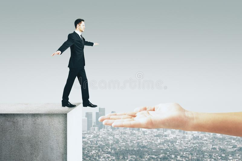 Teamwork and challenge concept. Hand helping businessman overcome gap on city background. Teamwork and challenge concept stock images