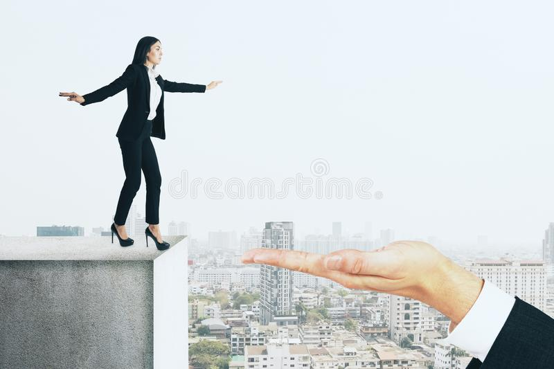Teamwork and challenge concept. Hand helping businesswoman overcome gap on city background. Teamwork and challenge concept stock image