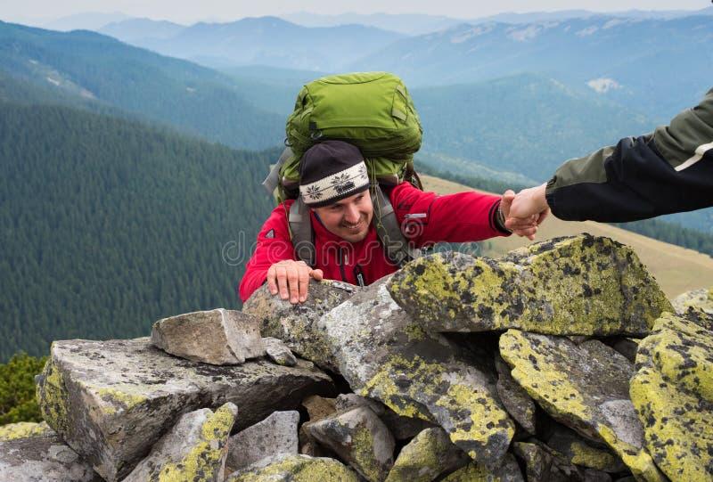 Hand helping hiker to climb the mountain stock photo