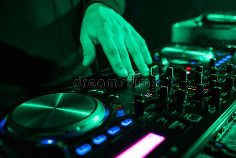 Hand het bewegen zich van de controlemechanismen van DJ op muziekcontrolebord in nachtclub stock foto