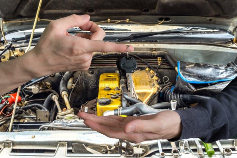 Hand het overhandigen autosleutels met vinger en hand die op eng ontvangen stock afbeelding