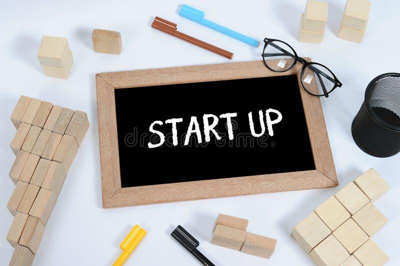 Hand het schrijven ?Opstarten ?op bord Bord, glazen, pengeval en houtsnede die als symbool van de staptrede van zaken stapelen stock afbeelding