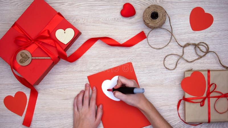 Hand het schrijven liefdewoord die op groetkaart op lijst met de vakjes van de ambachtgift liggen royalty-vrije stock foto
