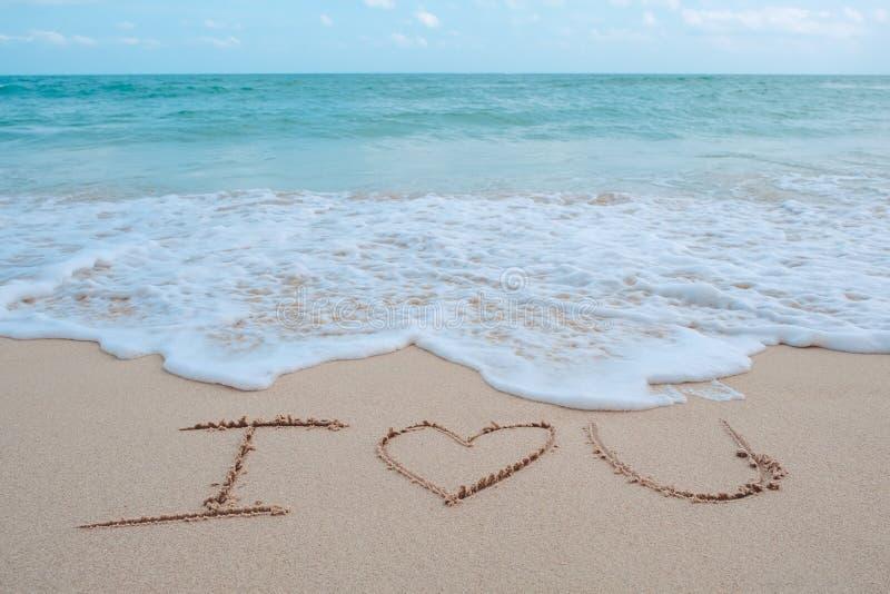 Hand het schrijven woord I houdt van u op het strand door het overzees met witte golven en blauwe hemel stock foto's
