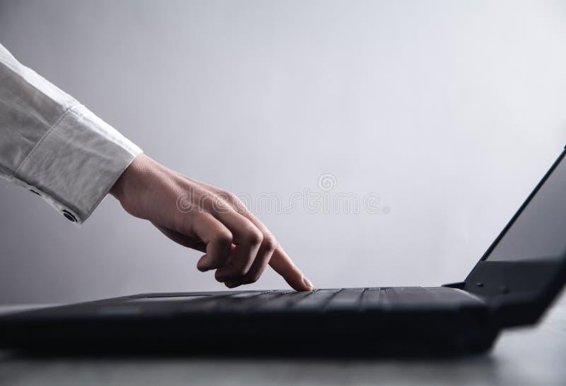 Hand het typen op laptop toetsenbord in bureau stock foto
