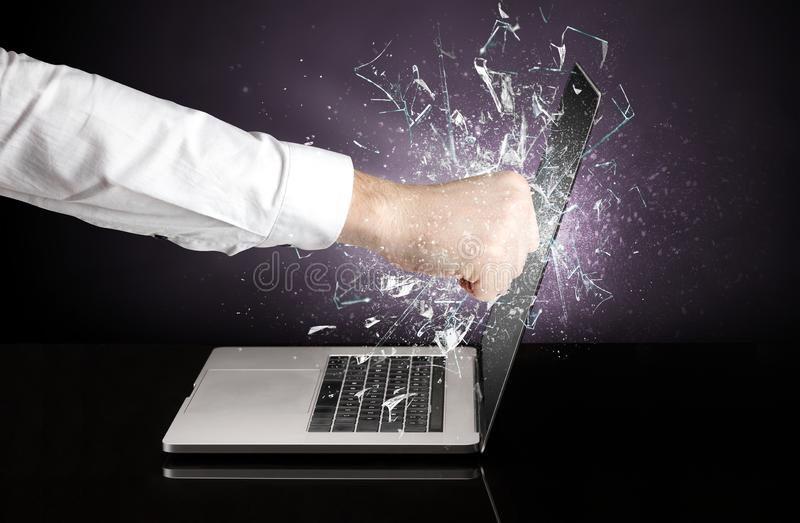 Hand hitting laptop screen screen. Hand hitting strongly laptop screen glass royalty free stock image