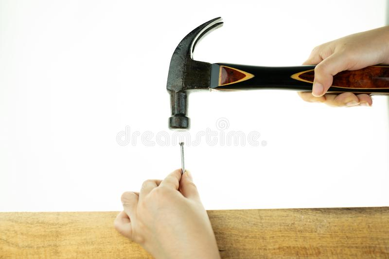 Hand hoiding hammer hitting a nail stock photography