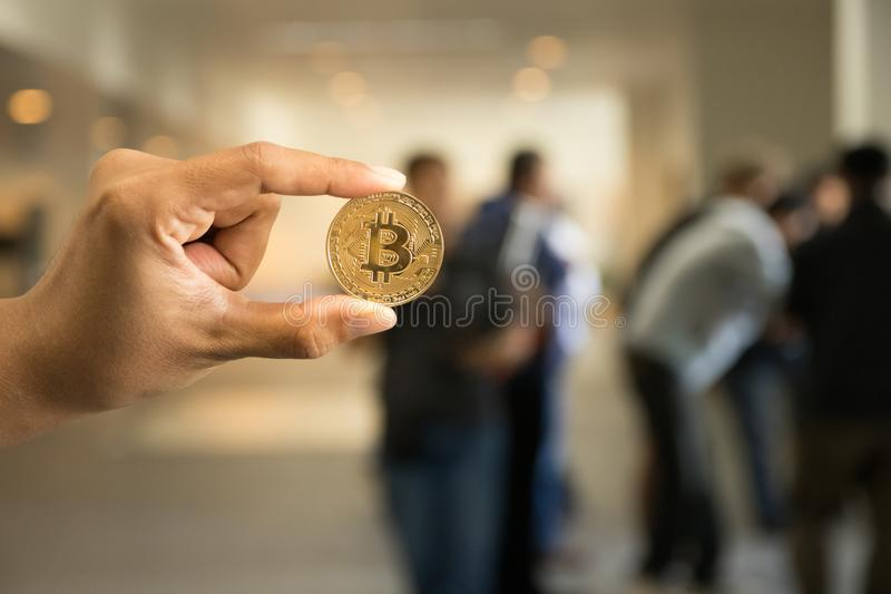 Hand hold Bitcoin on front blurred people meeting background royalty free stock images